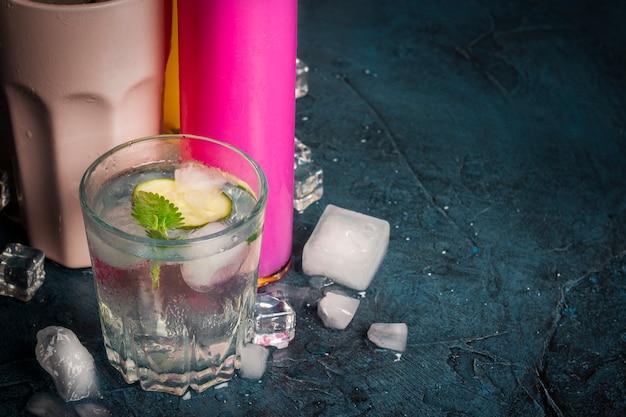 Четыре вида освежающих напитков со льдом на синей поверхности и кубиками льда. Premium Фотографии