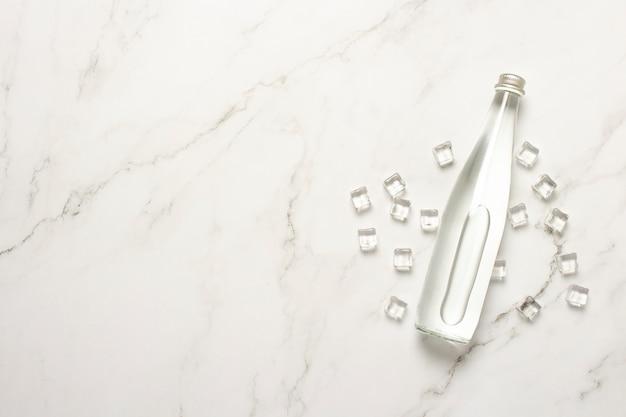 Стеклянная бутылка воды и кубики льда на мраморном столе. Premium Фотографии