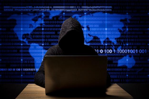 ラップトップでフード付きのジャケットを着たハッカーがテーブルに座っている Premium写真