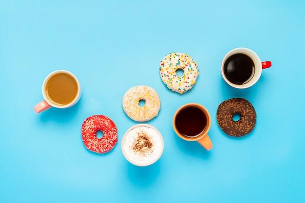 おいしいドーナツとカップと青い表面のホットドリンク。お菓子、ベーカリー、ペストリー、コーヒーショップ、友人、フレンドリーなチームの概念。フラット横たわっていた、トップビュー Premium写真