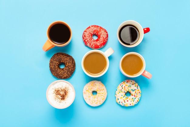 おいしいドーナツとカップ、ホットドリンク、コーヒー、カプチーノ、青い表面のお茶。 Premium写真