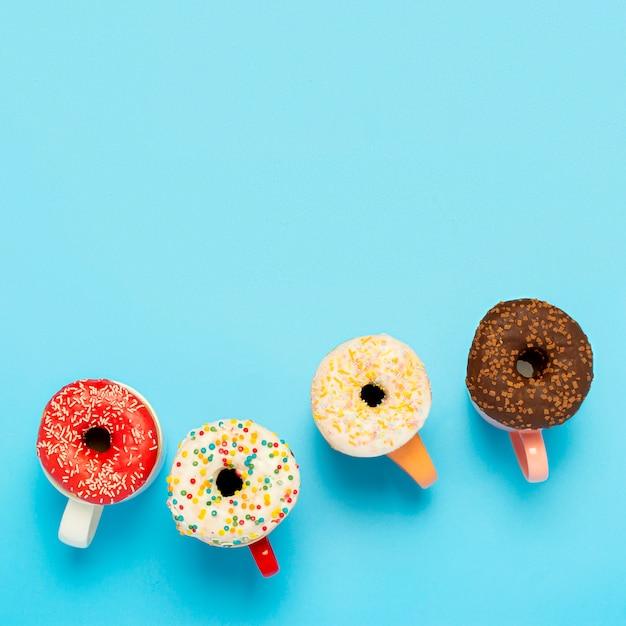 おいしいドーナツとカップと青い表面のホットドリンク。お菓子、ベーカリー、ペストリー、コーヒーショップの概念。平方。フラット横たわっていた、トップビュー Premium写真