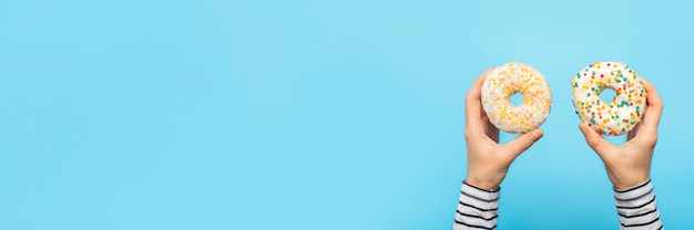 Женские руки держат пончики на синем. концепт кондитерский магазин, выпечка, кофейня. Premium Фотографии