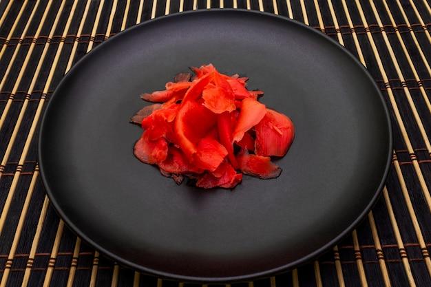 Маринованные ломтики имбиря в черной тарелке и бамбуковой циновке Premium Фотографии
