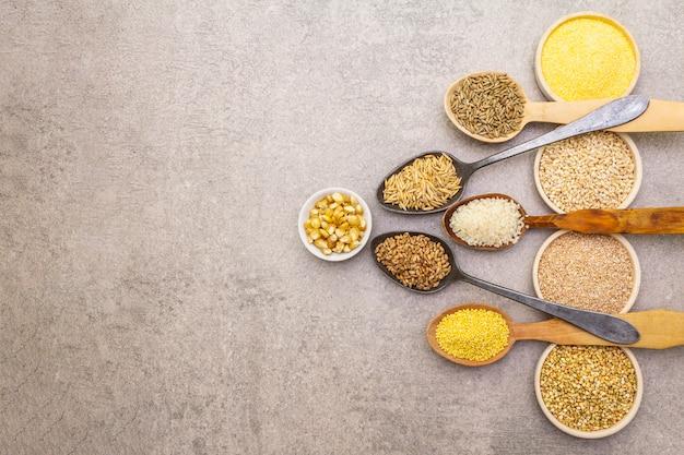 Ассортимент органических круп, бобовых и цельных зерен в мисках и ложках Premium Фотографии