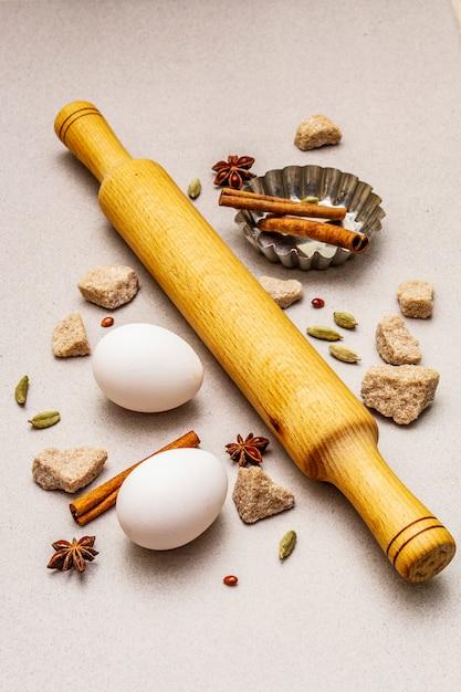 Рождественская кулинария, специи, яйца, коричневый кусковой сахар, форма для выпечки кекса и скалка. легкий каменный бетон Premium Фотографии