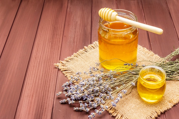 木製の蜂蜜ディッパーとガラスの瓶に新鮮な液体蜂蜜 Premium写真