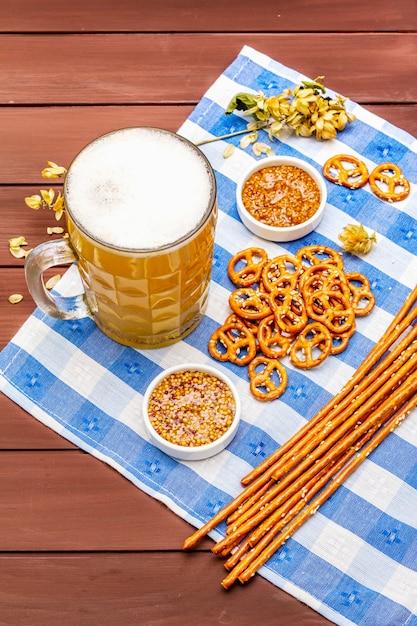 Октоберфест установлен. светлое пиво, крендели, горчица, кунжутная солома, хмель. Premium Фотографии