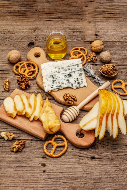 スモークチーズとブルーチーズ、クラッカー、蜂蜜、クルミ、熟した洋ナシのチーズプレート前菜 Premium写真