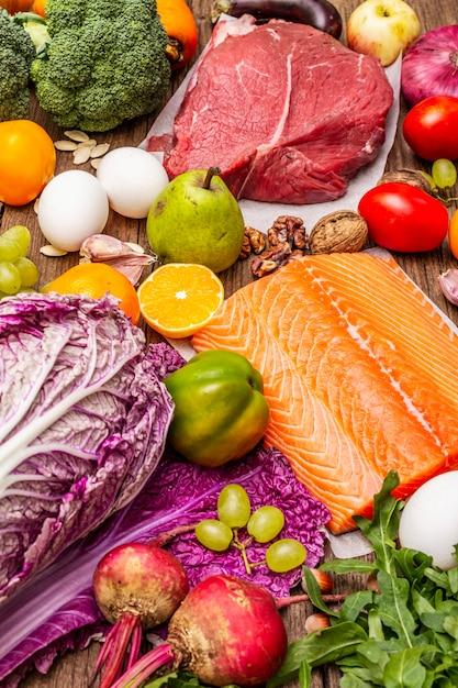 Тенденция к палео-пеганской диете. концепция здорового сбалансированного питания. набор свежих продуктов, сырого мяса, лосося, овощей и фруктов Premium Фотографии