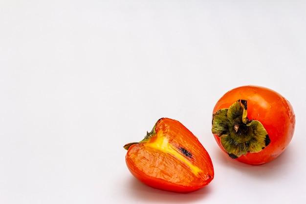 Спелая хурма. свежий целый фрукт, наполовину нарезанный. Premium Фотографии
