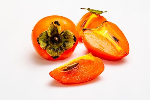 Спелая хурма. свежие целые фрукты, половина нарезанные, семена. Premium Фотографии