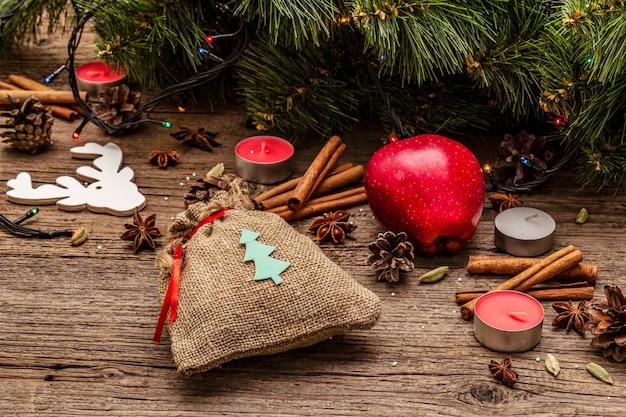 Подарок в мешочке, новогодняя елка, яблоко, свечи, специи, олень, шишки. природные украшения, старинные деревянные доски Premium Фотографии
