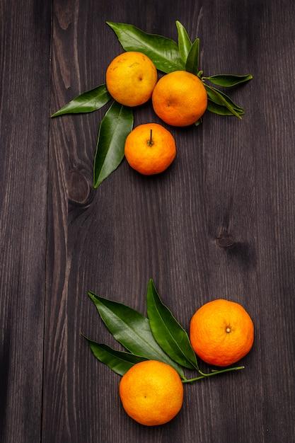 Свежие спелые мандарины с листьями на деревянный стол Premium Фотографии
