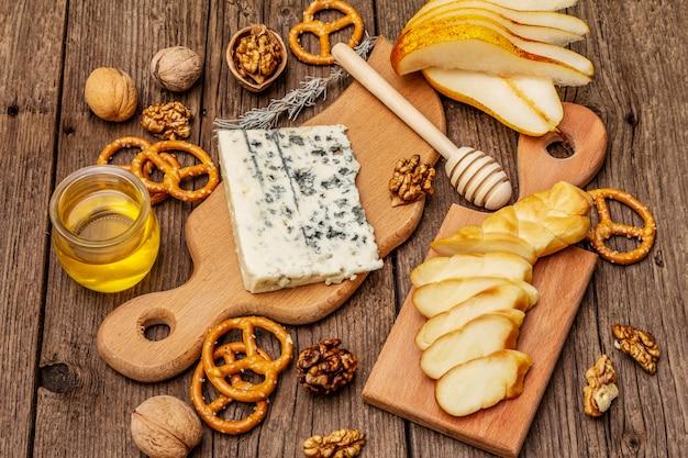 スモークチーズとブルーチーズ、クラッカー、蜂蜜、クルミ、熟した洋ナシのチーズプレート前菜。伝統的なスナックのレシピ Premium写真