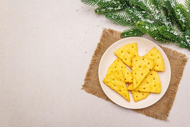 お祝いチーズクラッカー、新年のおやつコンセプト。クッキー、モミの木の枝、人工雪、荒布ナプキン。 Premium写真