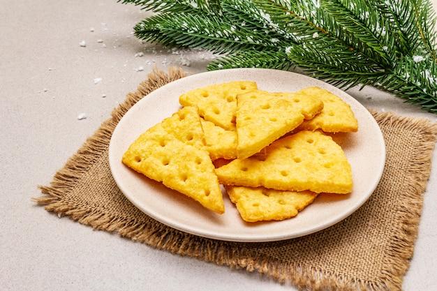 Праздничный сыр крекеры, концепция закуски новый год. печенье, ветка ели, искусственный снег, вретище салфетка. Premium Фотографии