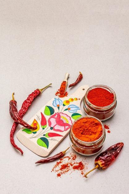 マジャール(ハンガリー)の赤くて甘いパプリカパウダー。まな板の伝統的なパターン、乾いたコショウのさまざまな品種。 Premium写真