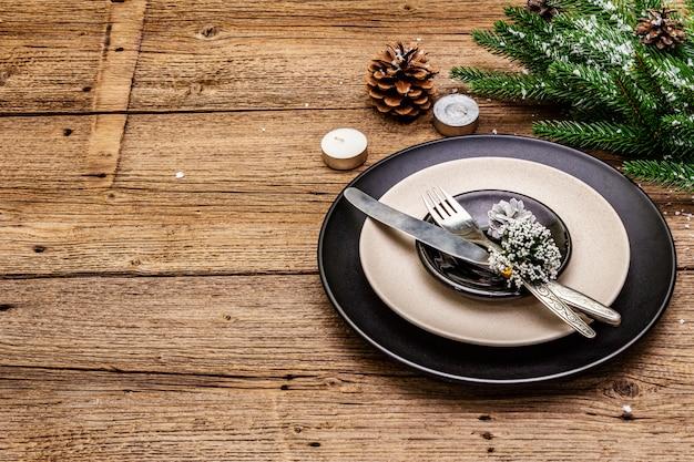 Урегулирование рождественского и новогоднего ужина вечнозеленая еловая ветка, свечи, шишки, керамические тарелки, вилка и нож. Premium Фотографии