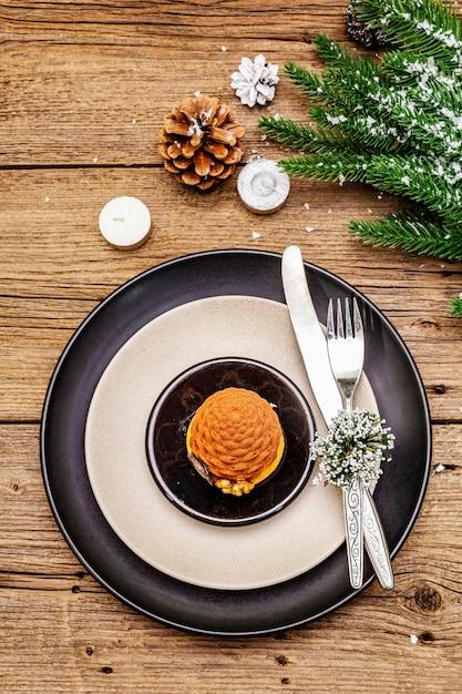 Урегулирование рождественского и новогоднего ужина сладкие закуски, ветка ели, свечи, шишки, керамические тарелки, вилка и нож. Premium Фотографии