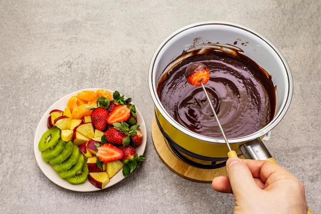 Шоколадное фондю. ассорти из свежих фруктов, два вида шоколада, мужская рука. ингредиенты для приготовления сладкого романтического десерта. Premium Фотографии