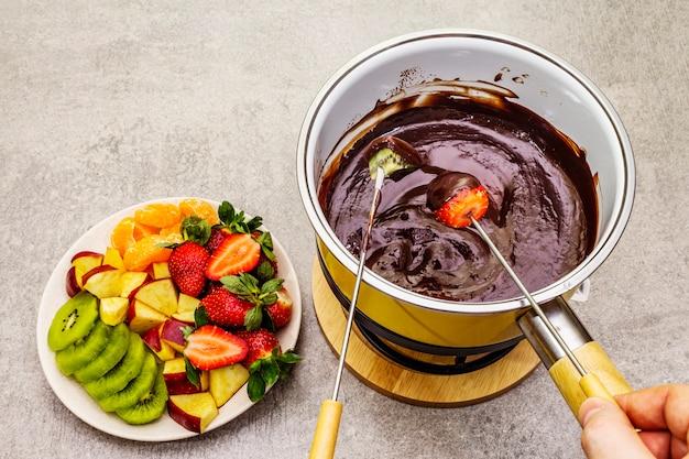 Шоколадное фондю. ассорти из свежих фруктов, два вида шоколада, мужская и женская рука. ингредиенты для приготовления сладкого романтического десерта. Premium Фотографии