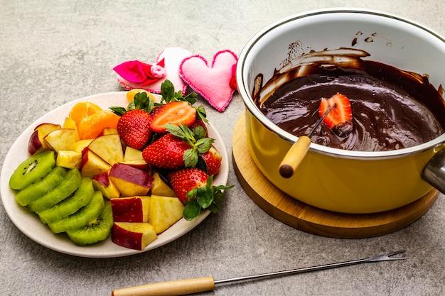 Шоколадное фондю. ассорти из свежих фруктов, два вида шоколада, войлочные сердечки. ингредиенты для приготовления сладкого романтического десерта. Premium Фотографии