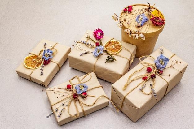 廃棄物ゼロギフトコンセプト。誕生日に優しいパッケージ。さまざまな有機装飾が施されたクラフト紙のお祝いボックス。 Premium写真