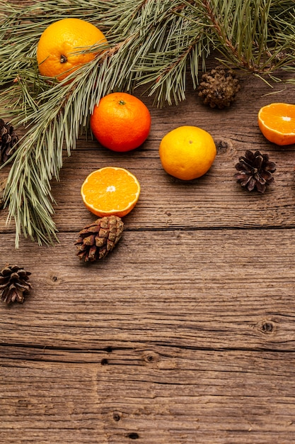 Дух рождества на деревянный стол. свежие апельсины, мандарины, сосновые ветки и шишки. природные украшения, старинные деревянные доски Premium Фотографии