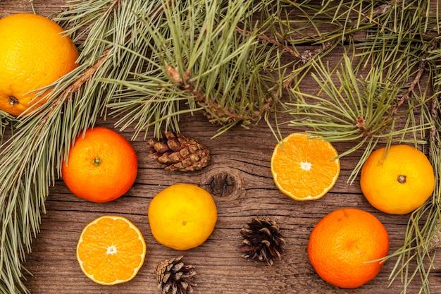 Свежие апельсины, мандарины, сосновые ветки и шишки. природные украшения, старинные деревянные доски Premium Фотографии