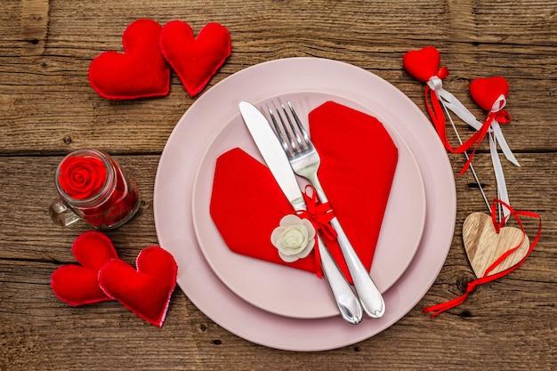 プレートとハート形のナプキンでロマンチックなディナーテーブル Premium写真