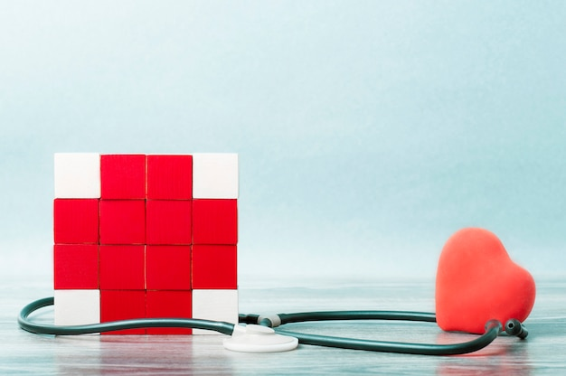 赤十字の形をした立方体のモザイクと、スタトスコープが絡み合っています。心臓の反対側に。医学の概念、ヘルプ。 Premium写真