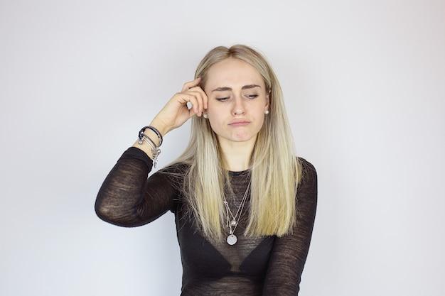 Современная девушка держит палец возле головы и думает Premium Фотографии