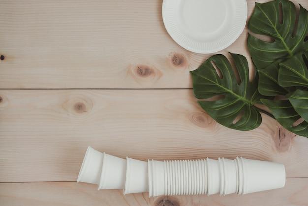 Бумажная пищевая упаковка, экологически чистые одноразовые, компостируемые, пригодные для переработки бумажные стаканчики и тарелка с растениями на деревянных фоне. Premium Фотографии