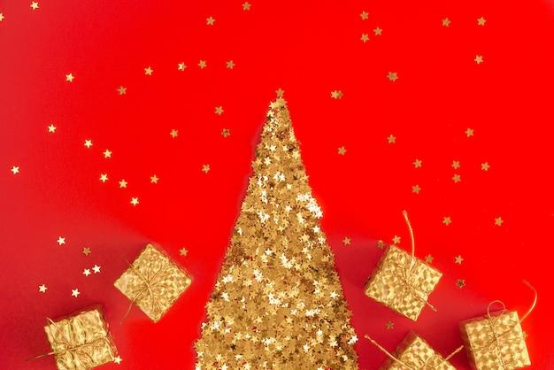 Праздничный абстрактный красный фон с небольшими золотыми декоративными звездами с блестками. Premium Фотографии