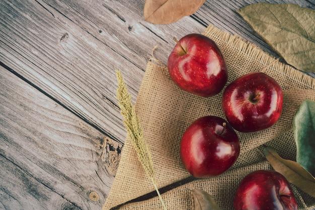 小麦粒の草と多くの乾燥した葉を持つ新鮮なジューシーな赤いリンゴは、古い木の板の表面の黄麻布の上にあります。トップビューフラットレイアウト構成。テキストテンプレート用のスペース Premium写真