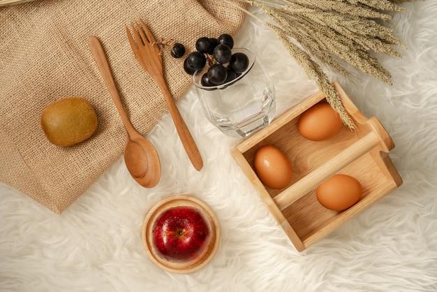 Яйца в деревянную корзину с свежие сочные красное яблоко на деревянные каботажное судно. Premium Фотографии