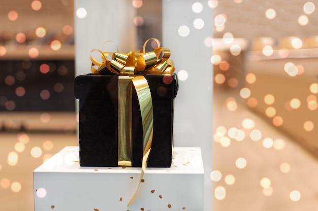 Большая подарочная коробка украшена золотой лентой лук на белом столе над яркими огнями боке. Premium Фотографии