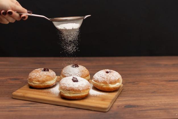 ハヌカ・スフガニヨット。ハヌカの伝統的なユダヤ人ドーナツと赤ジャムと砂糖の粉。 Premium写真