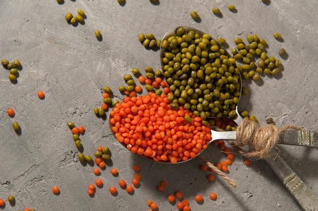 Ложки с красной чечевицей и бобами мунг на серой поверхности - суперпища, здоровая пища. Premium Фотографии