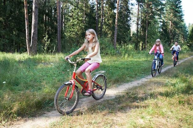 Дети катаются на велосипедах в лесу Premium Фотографии