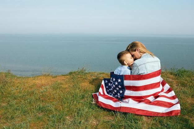 Мать-одиночка с сыном на день независимости сша. женщина и ее ребенок гуляют с флагом сша на берегу океана Premium Фотографии