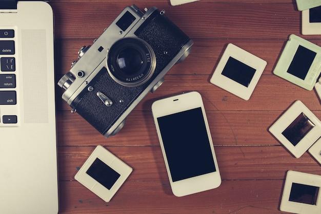 Ретро камера и несколько старых фотографий на деревянный стол Premium Фотографии