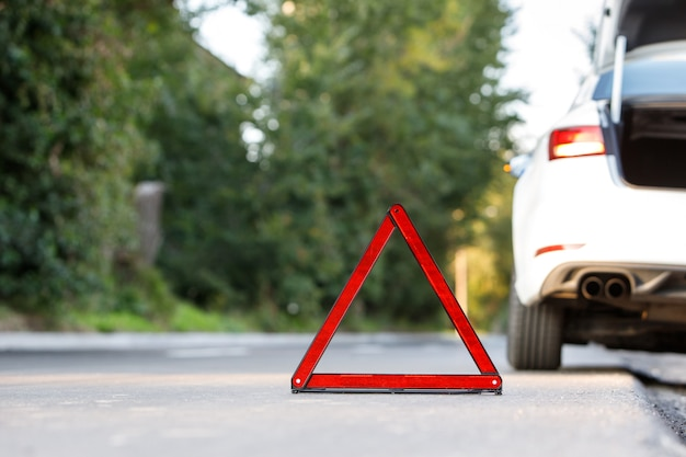 赤い警告トライアングルサインシンボルと道端で壊れた白い車のクローズアップ Premium写真