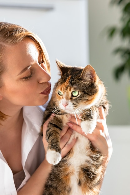 Улыбающаяся женщина в белой рубашке целует и обнимает с нежностью и любовью кота, держа ее на руках Premium Фотографии