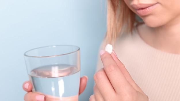 薬と水のガラスを取って不健康な若い女性のクローズアップ Premium写真