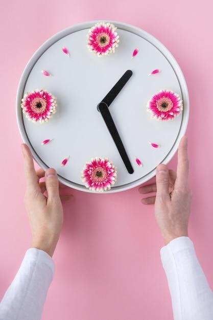 新鮮なピンクのガーベラの花から作成された白い時計を保持している男の手 Premium写真