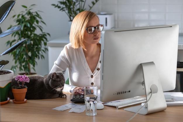 Женщина работает на компьютере из домашнего офиса в период самоизоляции, кошка спит рядом на столе Premium Фотографии