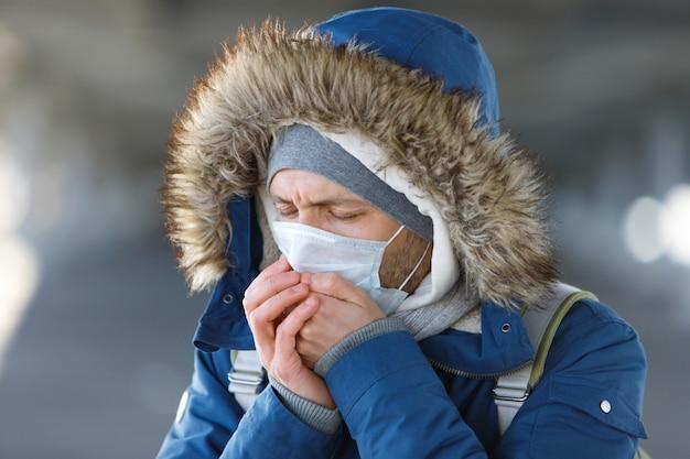 Человек чихает, кашляет, носит медицинскую защитную маску. Premium Фотографии