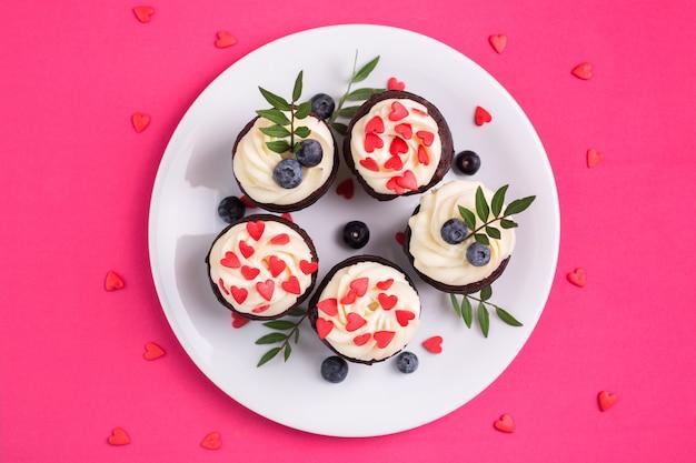ハートで飾られたカップケーキ。愛。バレンタインデーのコンセプトです。上面図。 Premium写真